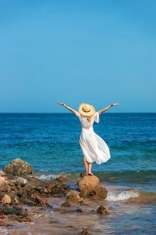 帽子をかぶった女性が海を見る
