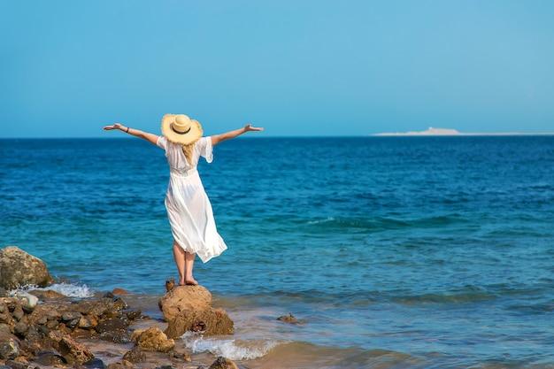 帽子をかぶった女性が海を見る Premium写真