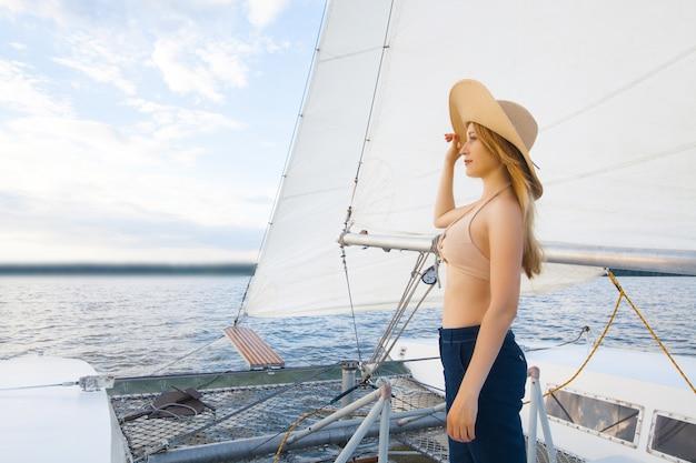 空と海を背景に、ヨットの帽子をかぶった女性。