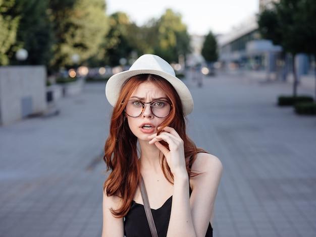 모자를 쓴 여자가 여름에 나무 근처 공원에서 길을 걷습니다.