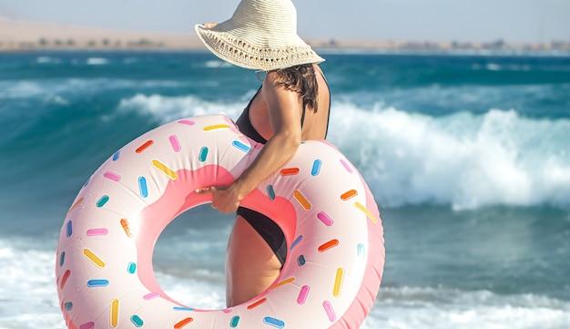 海のそばでドーナツ型の水泳サークルを持つ帽子をかぶった女性。休暇中のレジャーとエンターテイメントの概念。