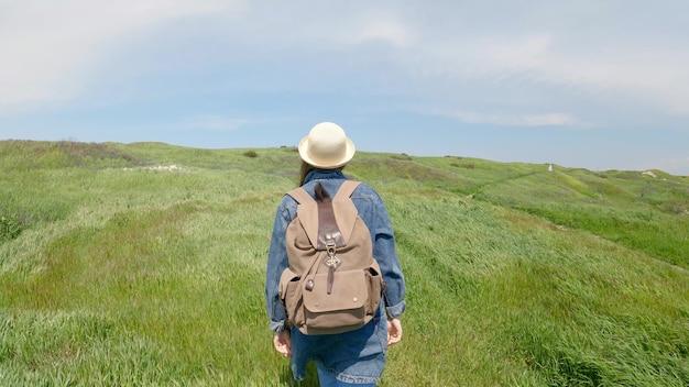 大きなバックパックをかぶった帽子をかぶった女性が、緑の芝生のある緑の牧草地を歩きます。風が草を揺らします。アクティブなレクリエーションと旅行のコンセプト。背面図、4kuhd。