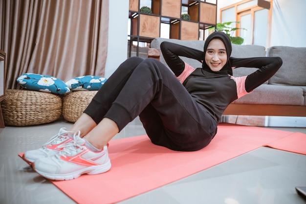 ヒジャーブのスポーツウェアを着た女性が腹筋運動をしながら微笑む自宅での活動中に腹筋を鍛える
