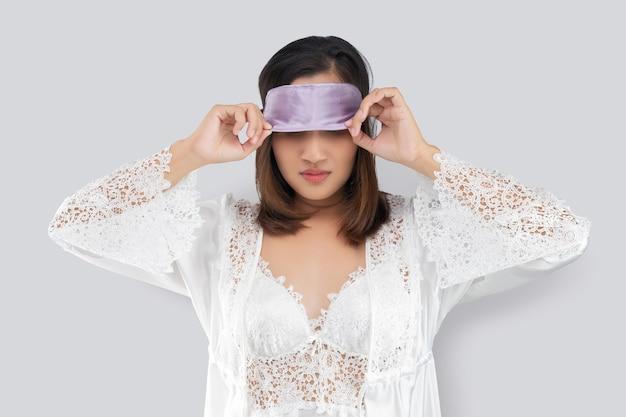 회색에 서있는 수면 마스크를 쓰고 레이스 잠옷과 흰색 실크 가운을 입은 여자