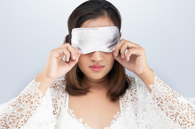 Женщина в кружевной ночной рубашке и белом шелковом халате в маске для сна стоит
