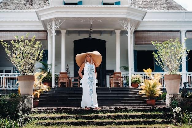 큰 모자와 긴 드레스를 입은 여성이 모리셔스 섬에서 포즈를 취합니다. 모리셔스 섬에 쉬고 아름다운 소녀.
