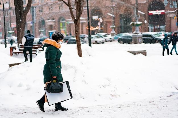 非常に雪に覆われた街の通りを歩いている財布とビニール袋の長いジャケットを着た女性。