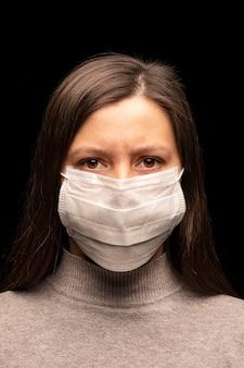 仮面の女性、緊張した落ち着きのない表情。コロナウイルス感染の懸念、保護の試み。スタジオポートレートのクローズアップ。縦写真