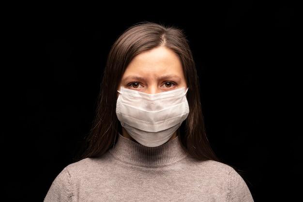 仮面の女性、緊張した落ち着きのない表情。コロナウイルス感染の懸念、保護の試み。スタジオポートレートクローズアップ