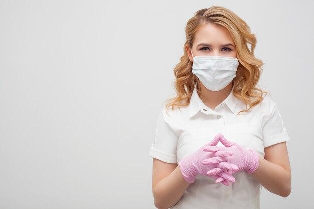 テキストスペースの右側に、仮面を被った女性と親しみやすい手袋をした女性がいます。コロノウイルス予防対策、感染予防、医療のコンセプト。