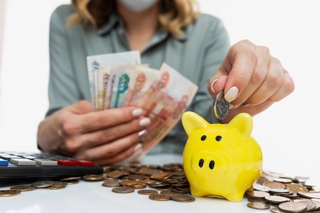 Женщина в маске держит в руке рубли и кладет монету в желтую копилку. инвестирование и сбережения. крупный план.