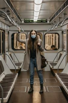 Женщина в медицинской маске во избежание распространения коронавируса держится за поручень в вагоне метро. девушка с длинными волосами в хирургической маске от covid-19 стоит в поезде метро.