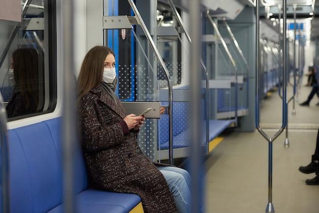 코로나 바이러스 확산을 막기 위해 의료용 마스크를 쓴 여성이 현대 지하철 차량에 스마트 폰을 들고 앉아있다