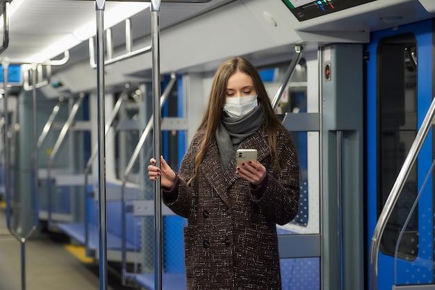 Женщина в медицинской маске, чтобы избежать распространения коронавируса, стоит и пользуется смартфоном в пустом вагоне метро.