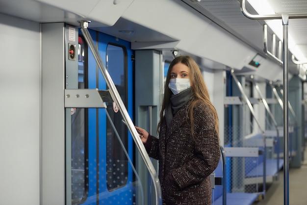 Женщина в медицинской маске, чтобы избежать распространения коронавируса, стоит возле дверей и смотрит в сторону в современном вагоне метро.