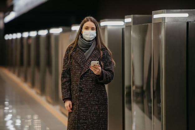 コロナウイルスの蔓延を防ぐために医療用フェイスマスクを着用した女性が電車を待っており、地下鉄の駅で携帯電話を持っています。サージカルマスクをした女の子が地下鉄で社会的距離を保っています。