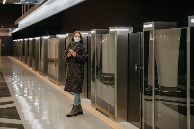コロナウイルスの蔓延を防ぐために医療用フェイスマスクを着用した女性が電車を待っており、地下鉄の駅でスマートフォンを持っています。サージカルマスクをした女の子が地下鉄で社会的距離を保っています。