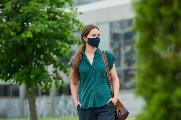 의료 얼굴 마스크에 여자 시내에서 바지 주머니에 손을 밀어 나무 사이 산책