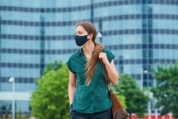 의료 얼굴 마스크에 여자는 주머니에 손을 밀어 걸어 시내에서 가방을 보유