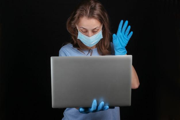 Женщина в медицинской маске и перчатках держит ноутбук на черной стене.