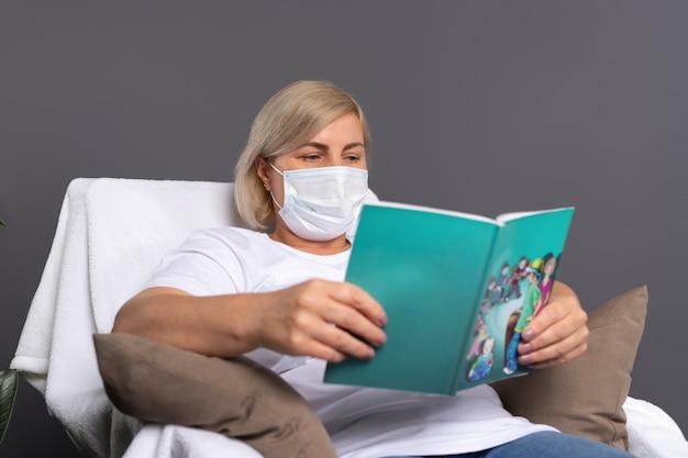 편안한 의자에 집에서 좋아하는 책을 읽고 의료 마스크에 여자