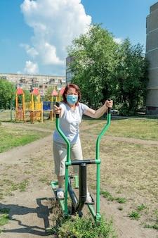 Женщина в медицинской маске работает на тренажере на спортивной площадке