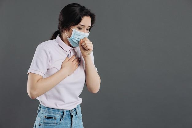 Женщина в защитной маске сильно кашляет. симптомы коронавиуса