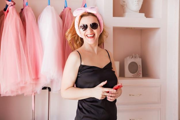 Женщина в розовой гардеробной своей квартиры, в солнечных очках, пижаме, стоит, смотрит в камеру и улыбается.