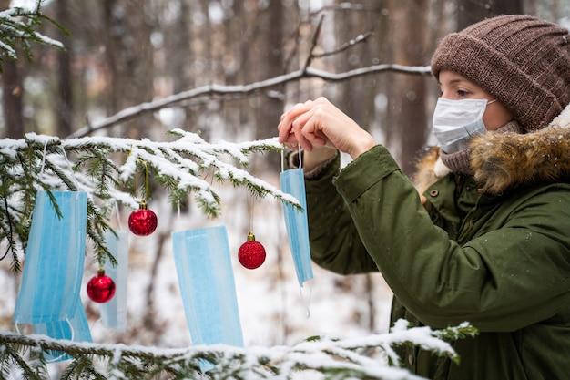 Женщина в защитной маске украшает растущую в лесу елку новогодними шарами и защитными масками