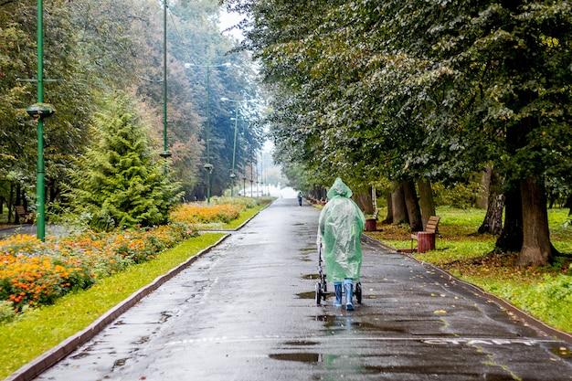 雨の中、乳母車を着たレインコートを着た女性が公園を散歩