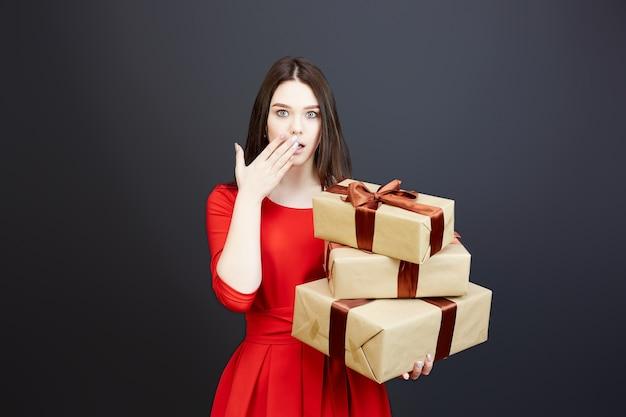 Женщина в красном платье удивленно открыла рот, держа в руках воздушные шары и подарочные коробки.