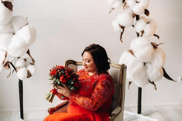 빨간 드레스를 입은 여성이 의자에 앉아 내부에 빨간 장미와 딸기 꽃다발을 들고 있습니다.