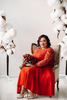 빨간 드레스를 입은 여성이 의자에 앉아 빨간 장미와 딸기 꽃다발을 내부에 들고 있습니다.