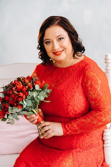 Женщина в красном платье сидит на диване и держит в интерьере букет красных роз и ягод.