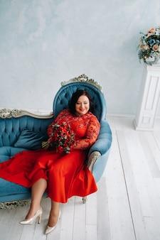 빨간 드레스를 입은 여성이 소파에 앉아 빨간 장미와 딸기 꽃다발을 실내에 들고 있습니다.