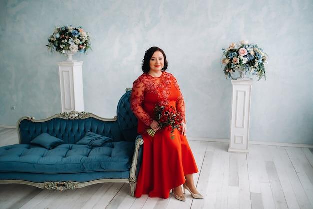 빨간 드레스를 입은 여자가 소파에 앉아 빨간 장미와 딸기 꽃다발을 내부에 보유하고 있습니다.