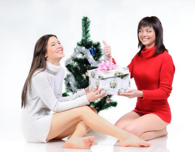 Женщина в красном платье сидит на полу возле елки. девушка в сером платье позирует с подарком в руках