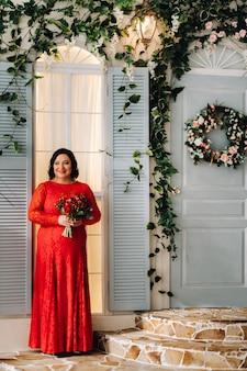 빨간 드레스를 입은 여성이 내부에 빨간 장미와 딸기 꽃다발을 들고 서 있습니다.