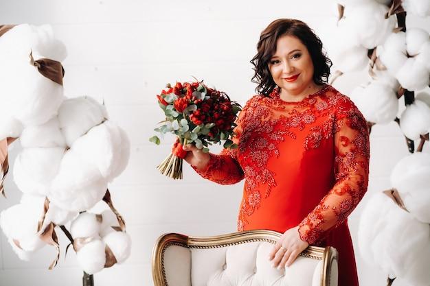 빨간 드레스를 입은 여성이 서서 내부에 빨간 장미와 딸기 꽃다발을 들고 있습니다.