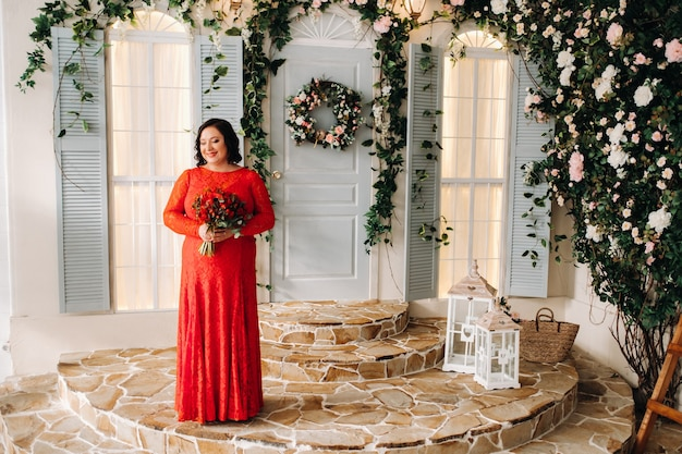 빨간 드레스를 입은 여자가 서서 내부에 빨간 장미와 딸기 꽃다발을 들고 있습니다.