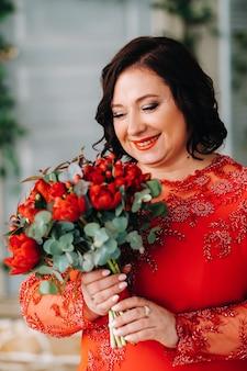 빨간 드레스를 입은 여자가 서서 빨간 장미와 딸기 꽃다발을 들고 있습니다.