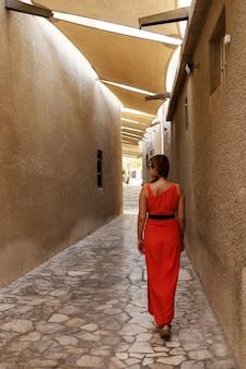 ドバイ旧市街のバスタキア地区の狭い通りを歩いている赤いドレスを着た女性