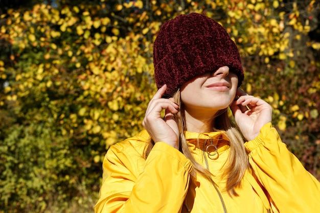 노란 가을 나무 앞 가을에 그녀의 눈 앞에서 빨간 모자를 쓴 여자. 확대. 가을 분위기