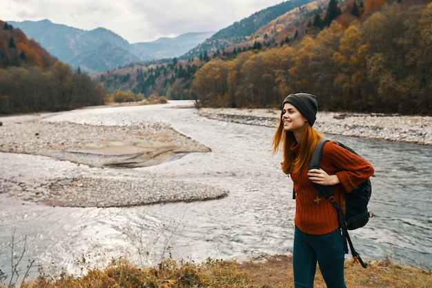 赤い上着を着た女性と背中のバックパックが山の川のほとりを歩いています。高品質の写真