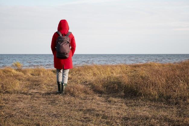 赤いジャケットを着た女性が泡の波を見る