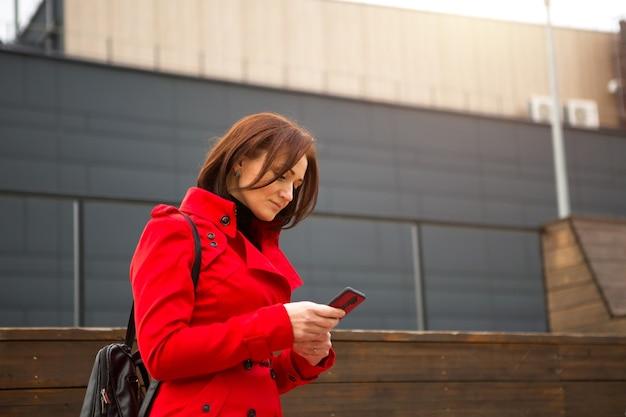 빨간 비옷을 입은 여성이 비즈니스 센터 근처에서 전화로 통화하고 있습니다. 가을이나 봄에 단발머리를 한 브루네트가 사업을 하고 원격으로 의사소통을 한다