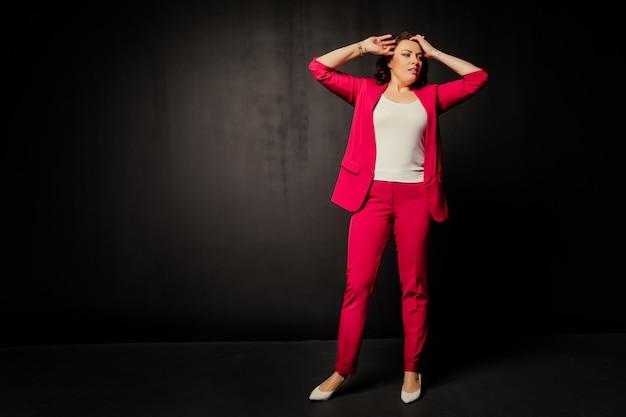 Женщина в красном костюме от удивления держится за голову и отводит взгляд