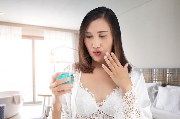 Женщина в атласной белой ночной рубашке и кружевном халате чувствует жжение во рту из-за того, что использовала жидкость для полоскания рта.