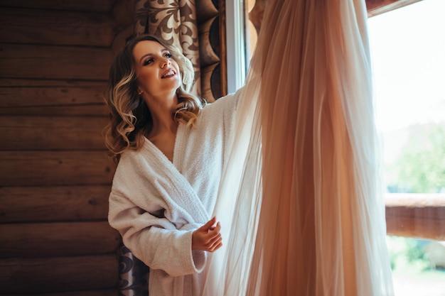Женщина в отдельном белом халате переодевается в платье. концепция свидания