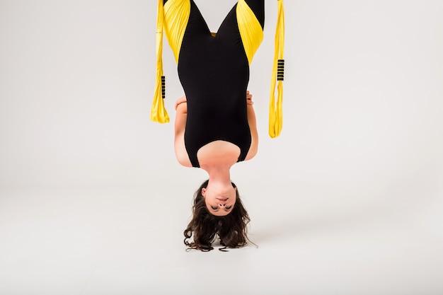 スポーツジャンプスーツを着た女性がエアヨガの練習をします